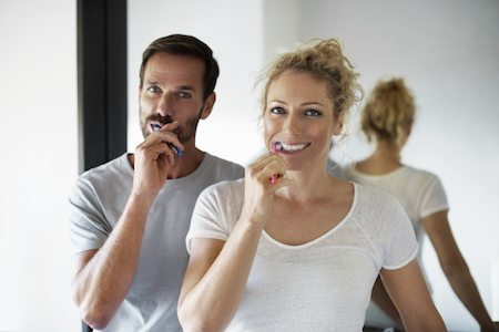 Couple brushing teeth after periodontal treatment